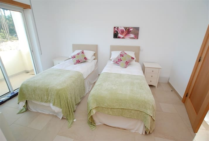 Fourth bedroom with 2 single beds and sliding doors opening to a large balcony