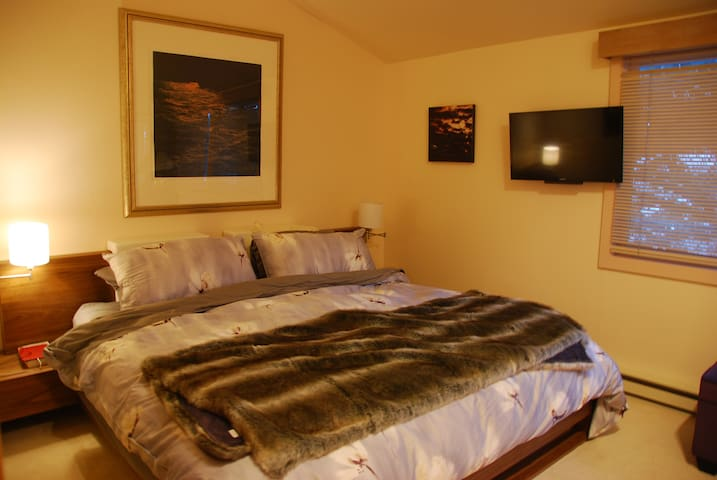 Master bedroom with king bed, luxurious bedding, air conditioning & en-suite bathroom
