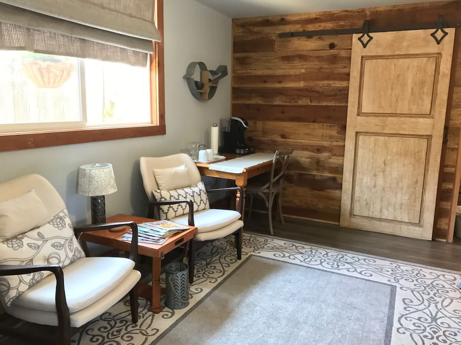 Sitting area, table and chair, barn door entry.