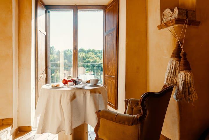 Zona Relax (2° piano): un tavolino per la colazione, una poltrona, due sedie e una portafinestra. Al mattino è il luogo ideale per fare colazione e godersi la vista sulla foresta di castagni.