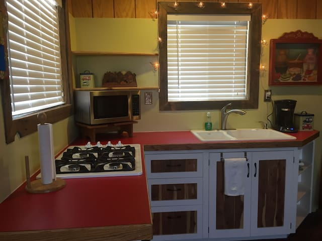 Dormitory sized refrigerator, four burner gas stove top, microwave, coffee maker with a permanent filter, and plenty of dishes, silverware, etc for your vacation needs.