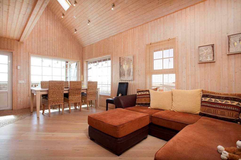 The main room in the cabin. Large welcoming sofa and Tv, dining room and kitchen. Amazing view to pure Icelandic nature and the ocean