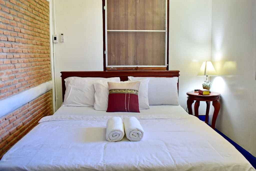 Top floor Balcony bedroom; Queen sized double bed, blackout wooden shutters, bedside table & lamp; ever changing mountain and seasonal water views