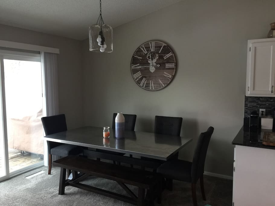 Dinning room table is stainless top with four chairs and a bench. Dimmable light above.