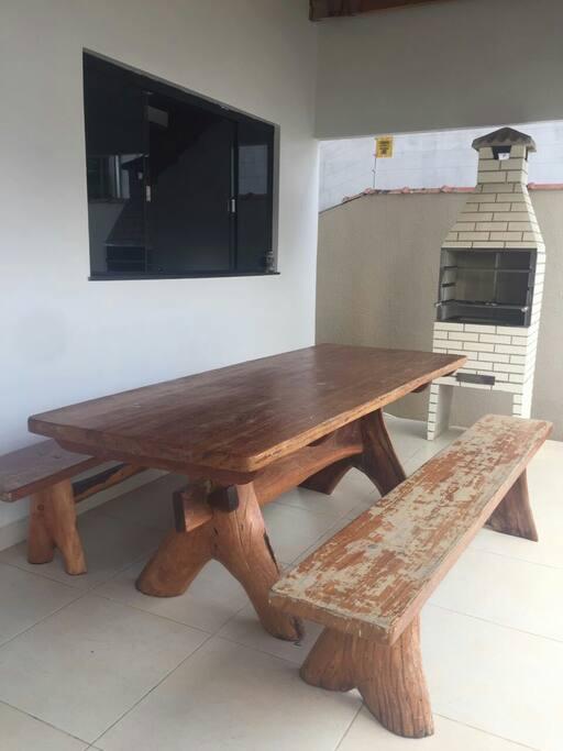Área de lazer com churrasqueira e mesa rústica