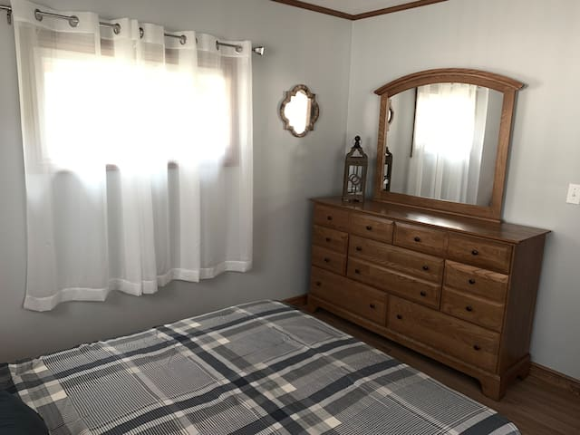 Bedroom features a full size bed, dresser and two night stands