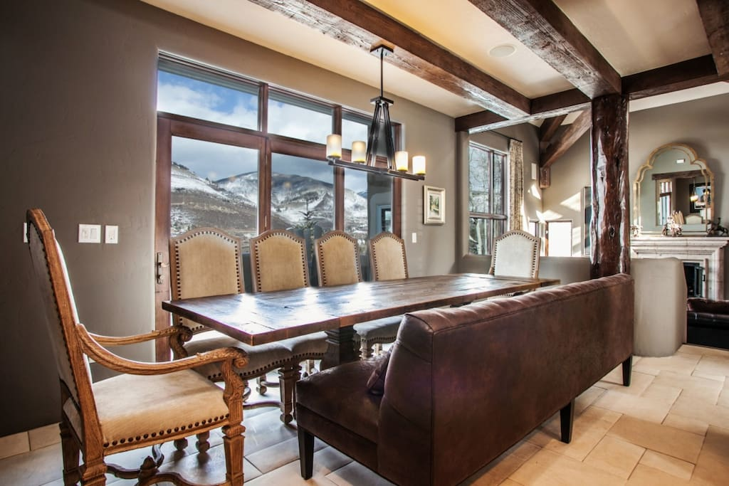 Located next to the kitchen, large dining table for 10 with oversized bench seating and gorgeous mountain views.