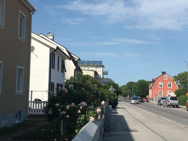 Huset ligger till vänster. Vid träden ligger ringmuren. Runt omkring ligger villor i ett lugnt område. Fri parkering på gatan.