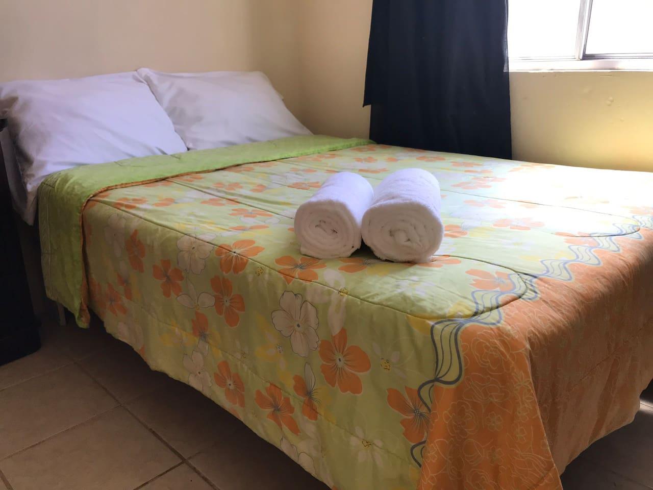 Cama, almohadas y toallas de baño.