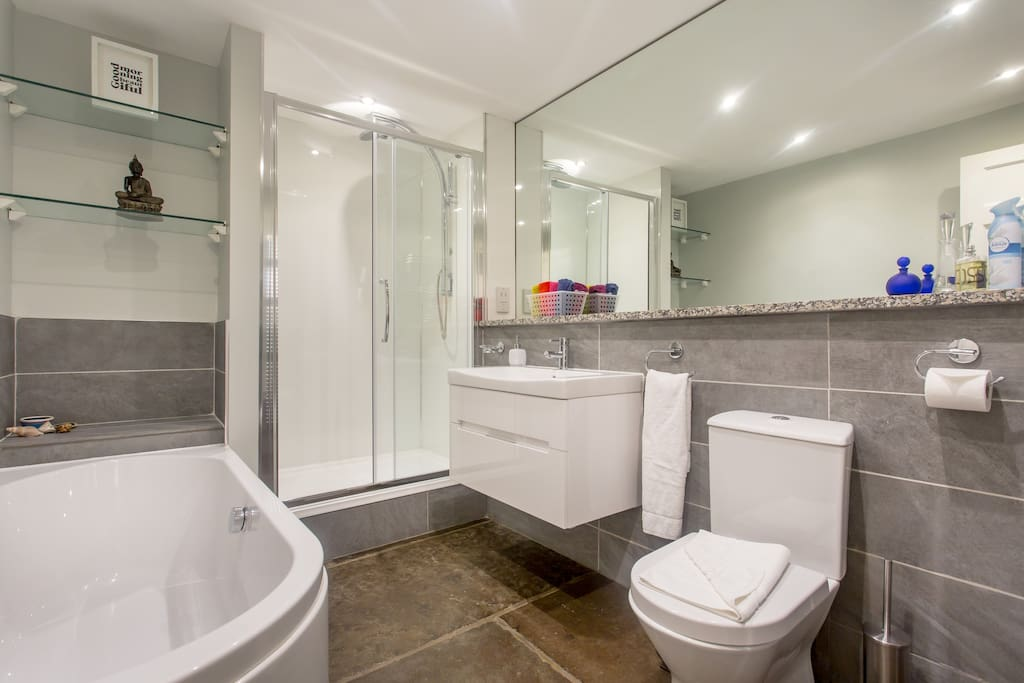 Bathroom with rainwater shower, large bath and underfloor heating. Heated mirror.