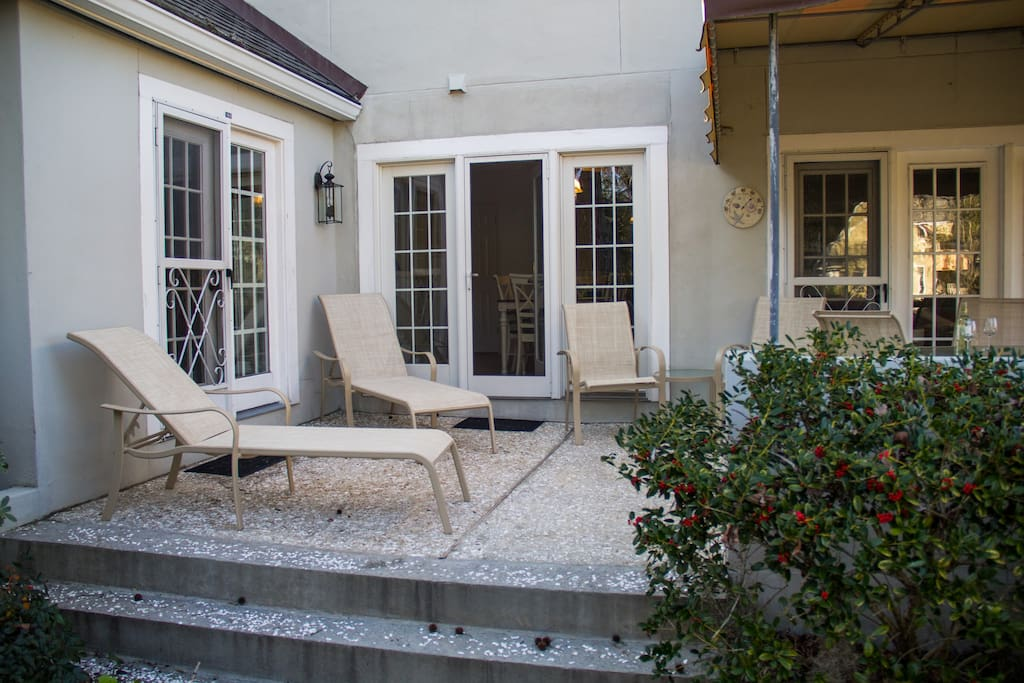 Comfortable patio that includes covered and uncovered areas with lounge chairs and a dining table.