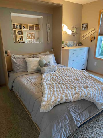 3rd bedroom featuring a cozy queen bed downstairs with bathroom and living room on the same level.