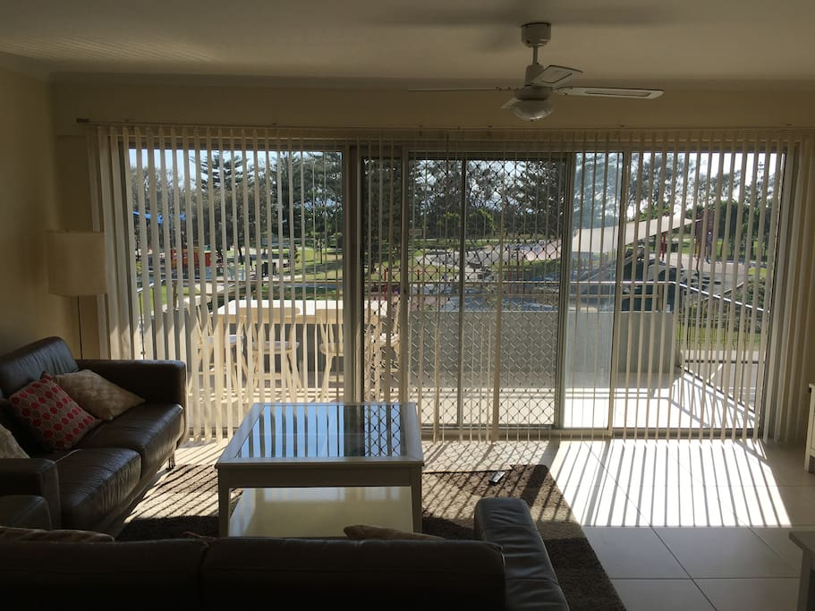 Open plan dining area and lounge with balcony overlooking the park and beach