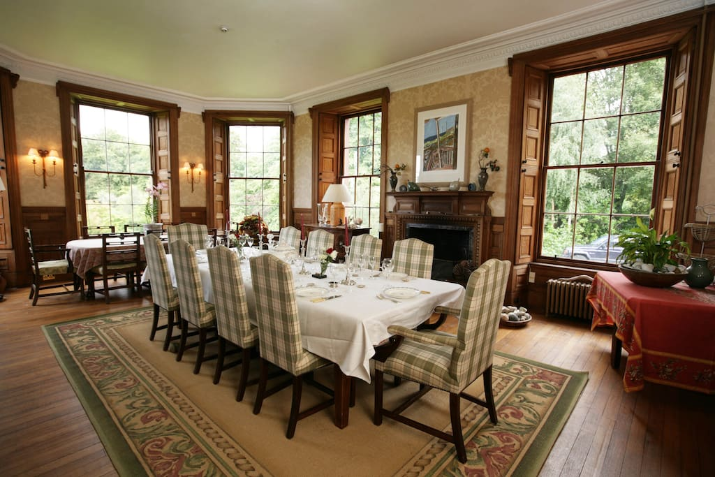Dining room with 2 tables seating 20 people. A large fireplace