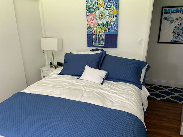 Queen size guest bedroom with smart tv mounted on wall