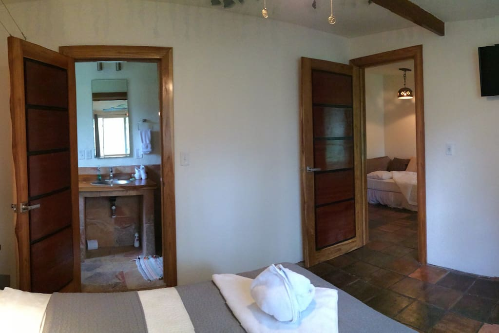 Mini panorama of the room with the queen sized bed, entrance to private bathroom and entrance to living space