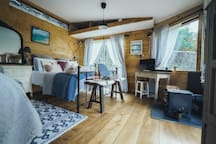 Open plan studio cabin, beautiful light from all windows nestled beside the waterfall. The perfect place to relax and reconnect with nature. Decorated with rustic charm with modern amenities:-) cosy woodburner , kitchenette  and seating area