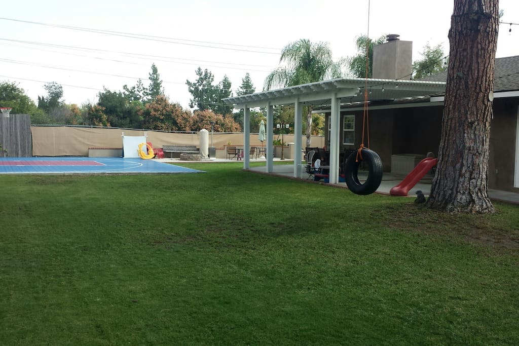 Large yard and patio with basketball court.