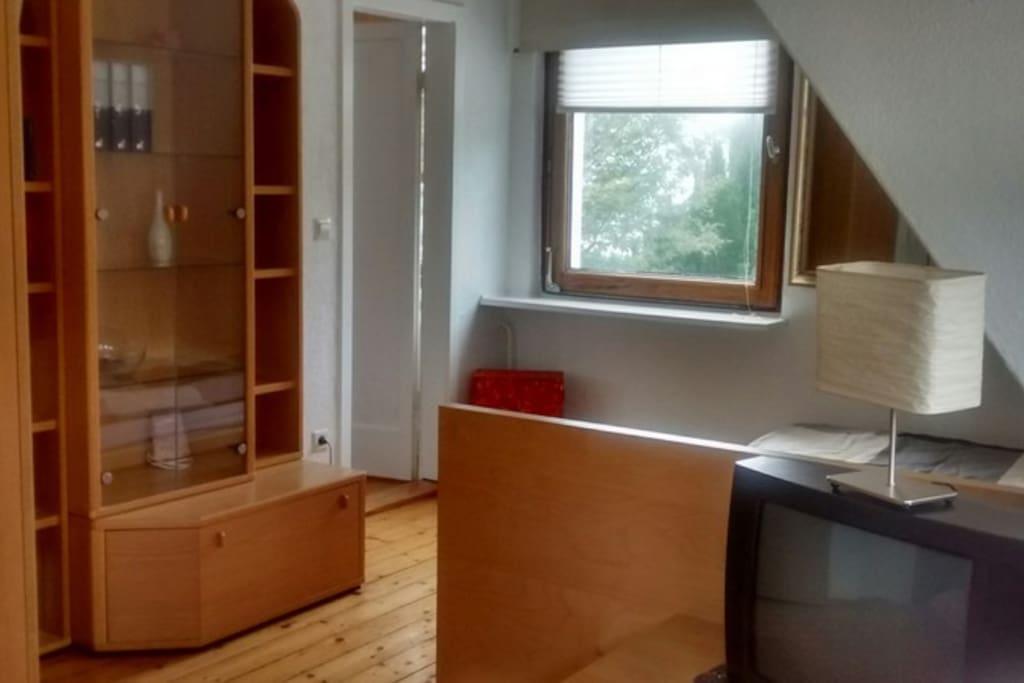Schlafzimmer mit Holzdielen und Verbindungstür zur Wohnküche