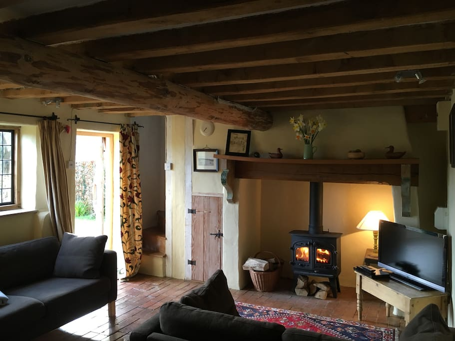 Living room with original beams and large inglenook fireplace - there is plenty of wood available for burning in the fireplace