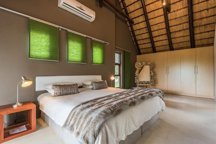 Upstairs main bedroom with ensuite bathroom, slidingdoor opening onto the balcony with garden views