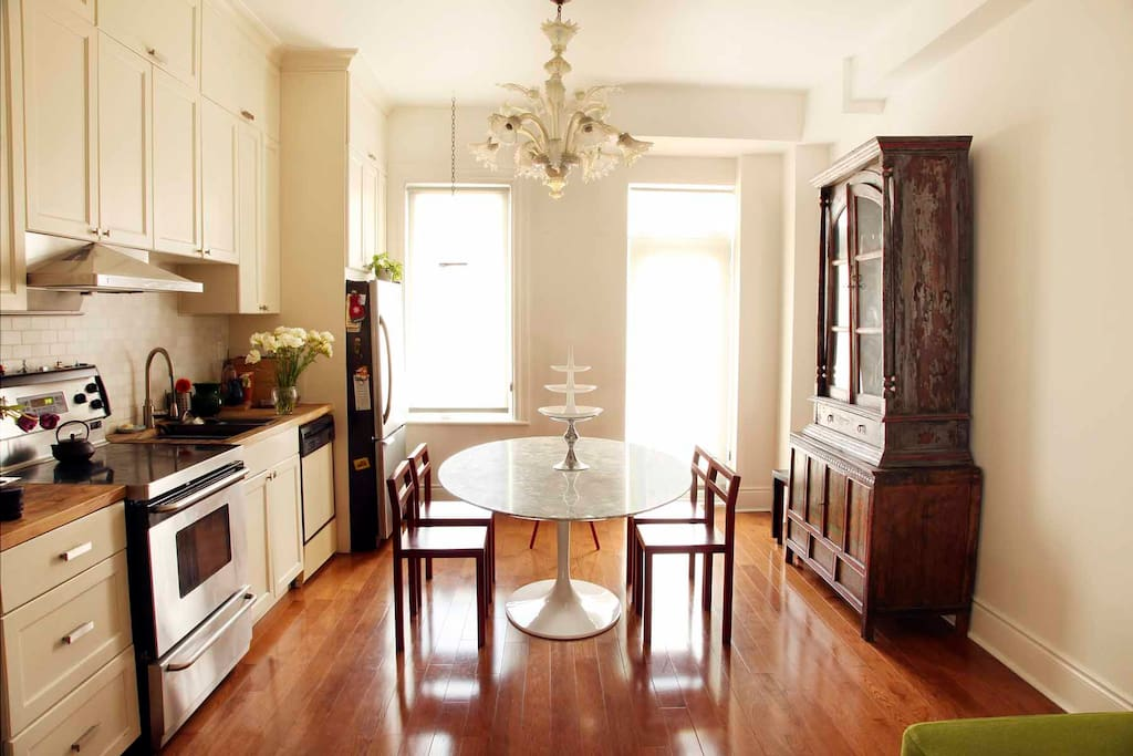 The bright custom-designed, fully equipped kitchen with new stainless steel appliances and butcher-block counters provides seating for six around a stunning vintage marble-top dining table. Oversize east-facing windows and a Juliet balcony off kitchen.