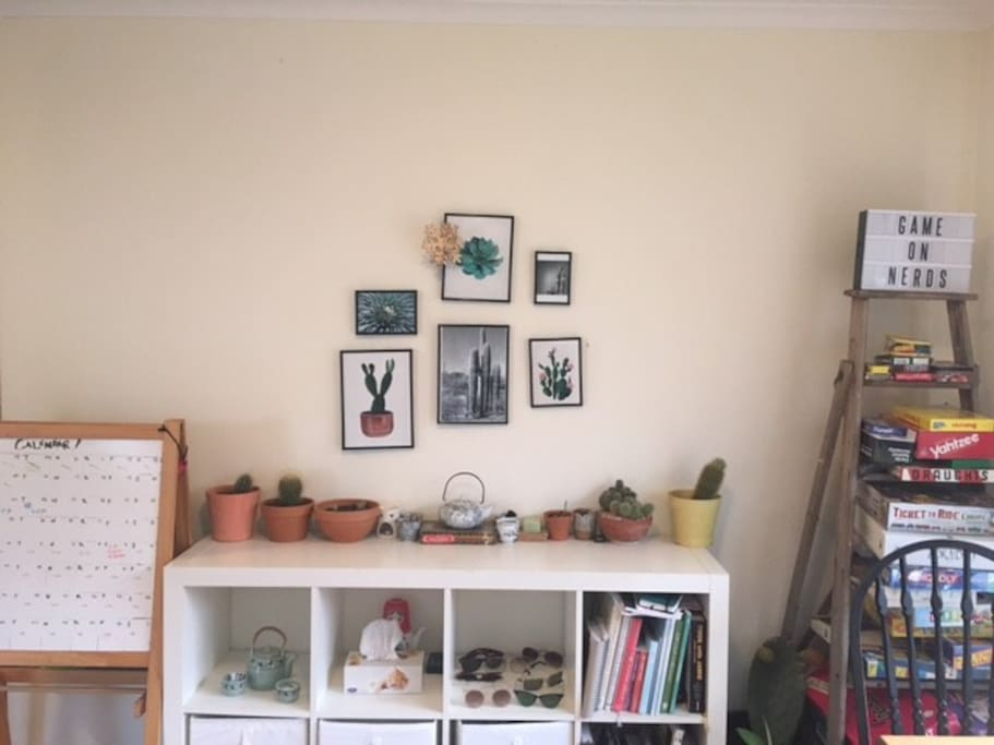 Living room/dining space wall with board games, cook books and cacti