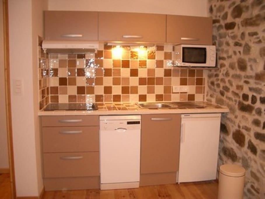 Cuisine équipée : lave-vaisselle, gazinière, micro-onde et réfrigérateur.