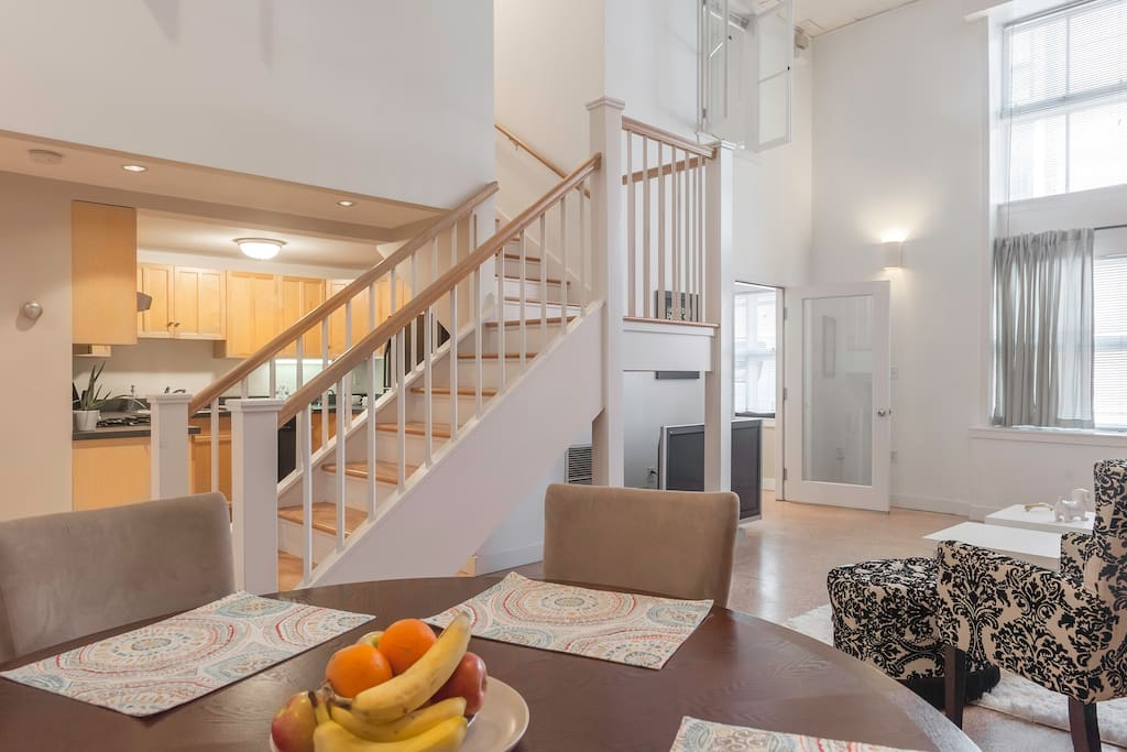 Airy and dramatic living space, stairs lead upstairs to the two bedrooms