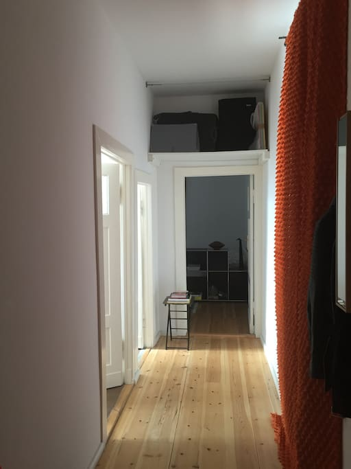 Long corridor with closet, storage, chair, table and hall stand.
