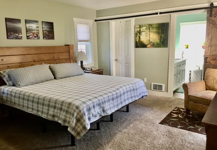 Master bedroom with king bed, dresser, sitting chair, small work space, TV, private bath and direct access to the hot tub. Please note there is no closet available in the master bedroom!!