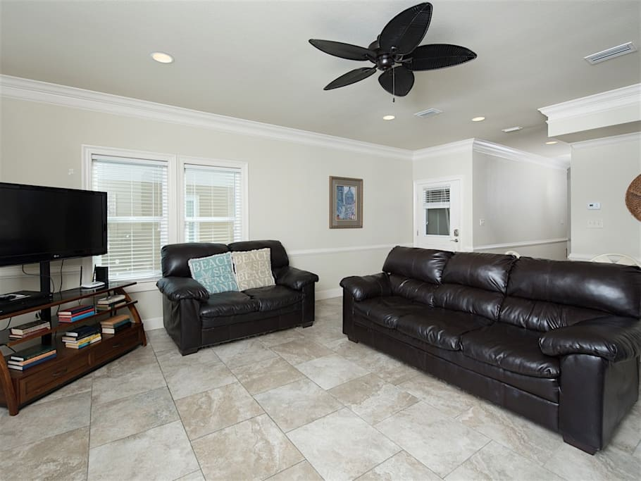 Relax on the comfortable black leather couches in the living room