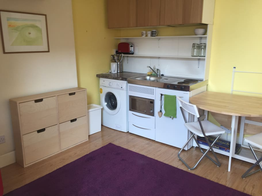 Kitchen area with all you need: fridge, washing machine, microwave etc.