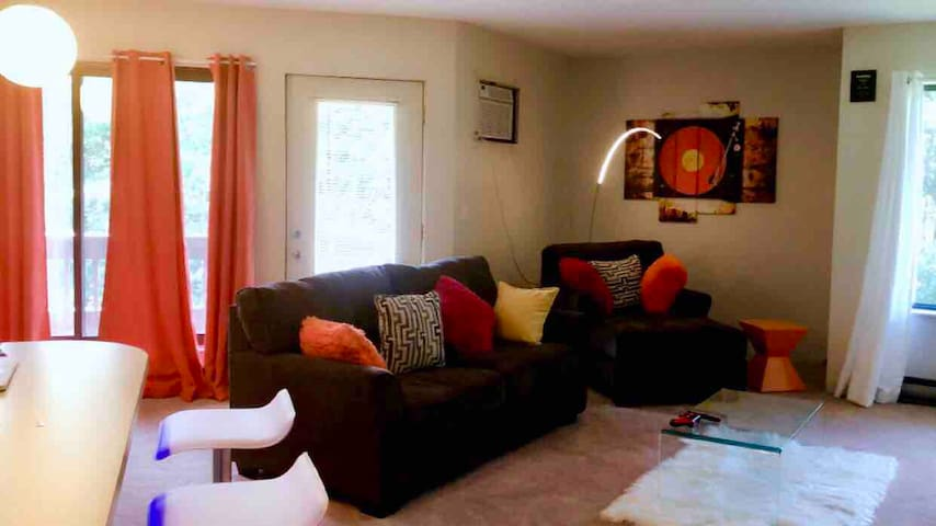 """Beautiful Spacious Living room Wall mounted 82"""" inches QLed TV Comfortable Couch Lots of faux throw pillows Air conditioner  Free Netflix Free fast WiFi Spacious walk area Counter Table with Barstools  Beautiful Overhead Light for reading"""