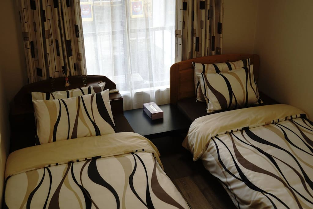 Room 2 with 2 single sized beds and in between is a low table that you can place your phones, eye glasses or any small things on it.
