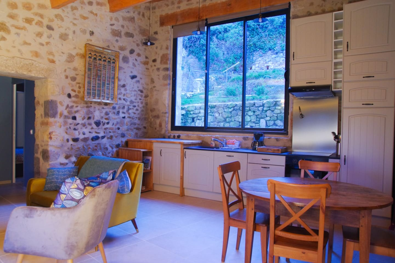 pièce principale avec coin salon et cuisine équipée, pierres et charpente apparentes