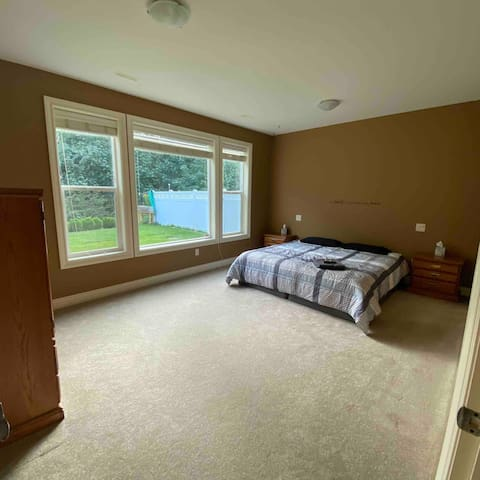Spacious bedroom with king size bed and walk-in closet. Two bedside tables and a chest of drawers. Large picture windows (not overlooked) looking out onto the garden with a view of the mountain.