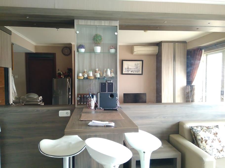 Tampak depan dari ruang tamu. Terlihat disini dilengkapi wallpaper dan juga kaca di sisi dindingnya serta meja, kursi dan juga lemari kecil untuk menaruh pajangan yang membuat nilai estetika di ruang tamu tersebut.