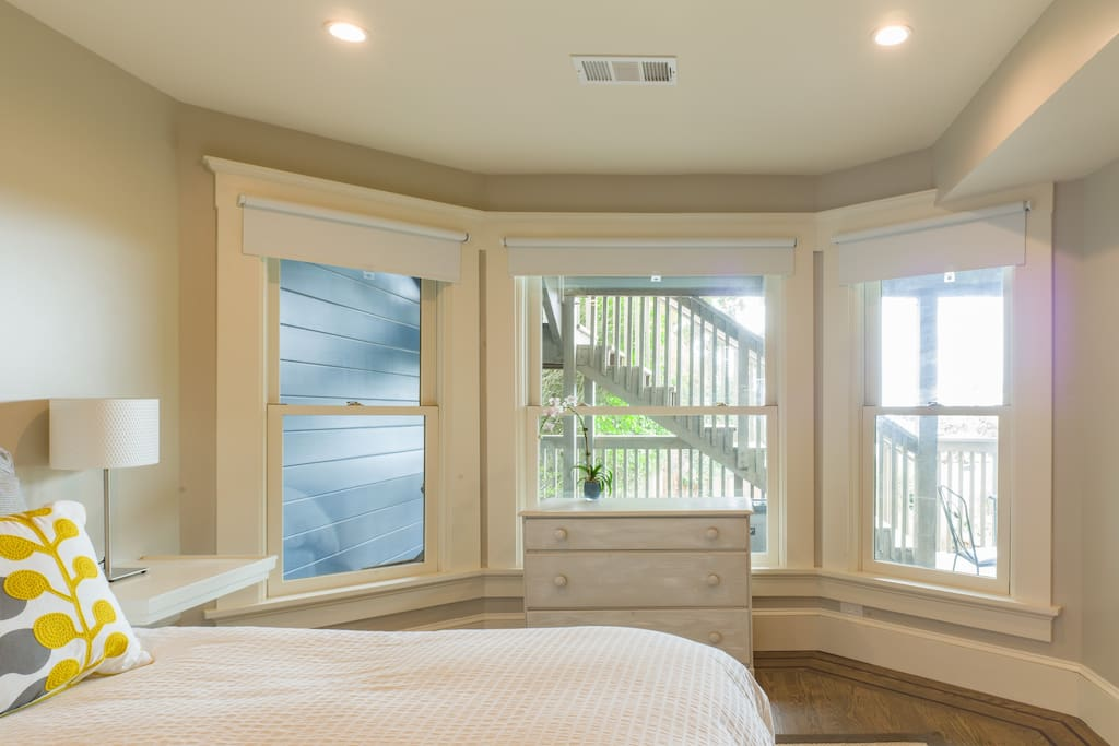 Sunny bedroom overlooks porch, with city views.