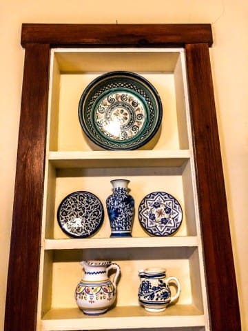 Some of the pottery our family has collected from Spain, displayed on a high shelf.