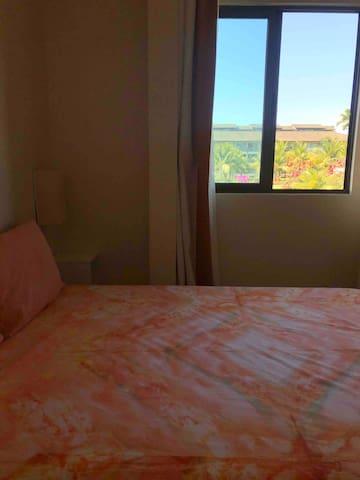 Quarto 1 com cama de casal e vista para área da piscina