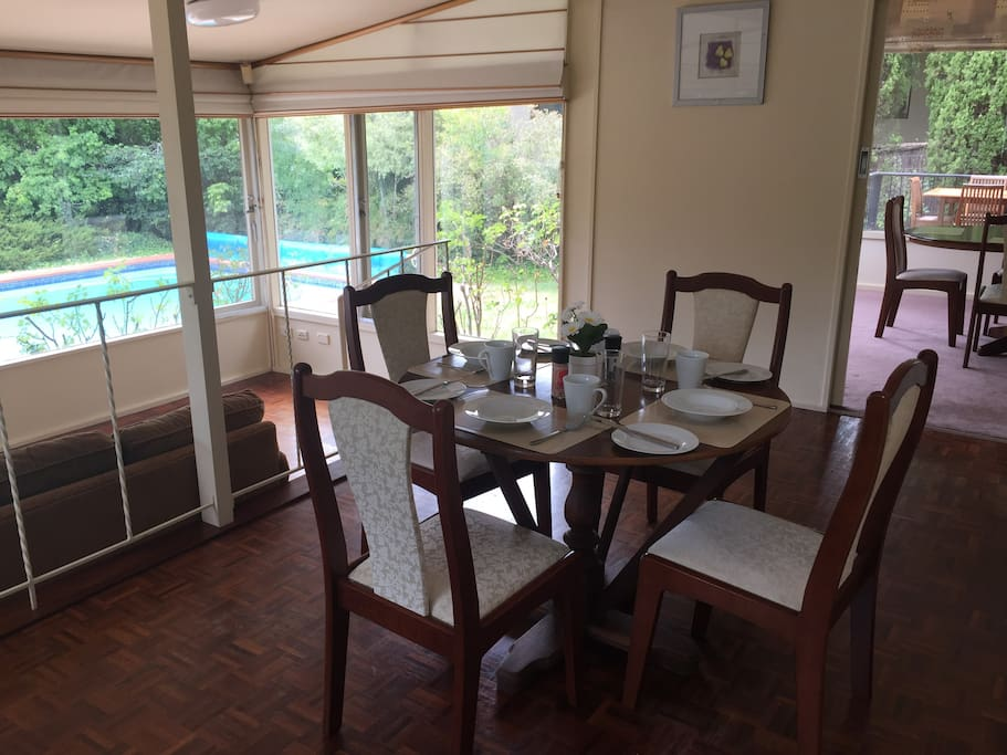 Small dining table off kitchen looking back over sun room and pool