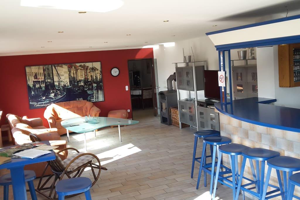 Unser großes Wohnzimmer mit Kaminofen, Theke und Balkon