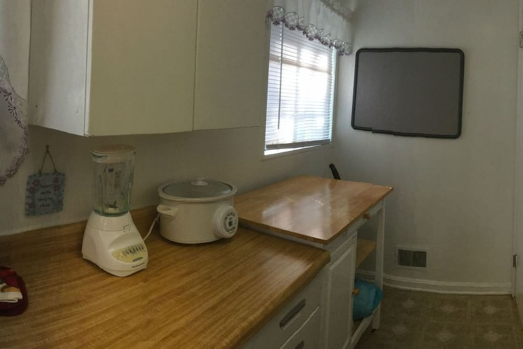 Galley Kitchen with Dishware, full stove, Microwave, Cookware.