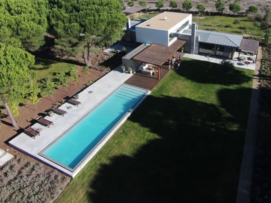 An outside lounge equipped with sofas and a wooden deck extends into the swimming pool surrounded by lavender and fruit trees as well as the pine trees.
