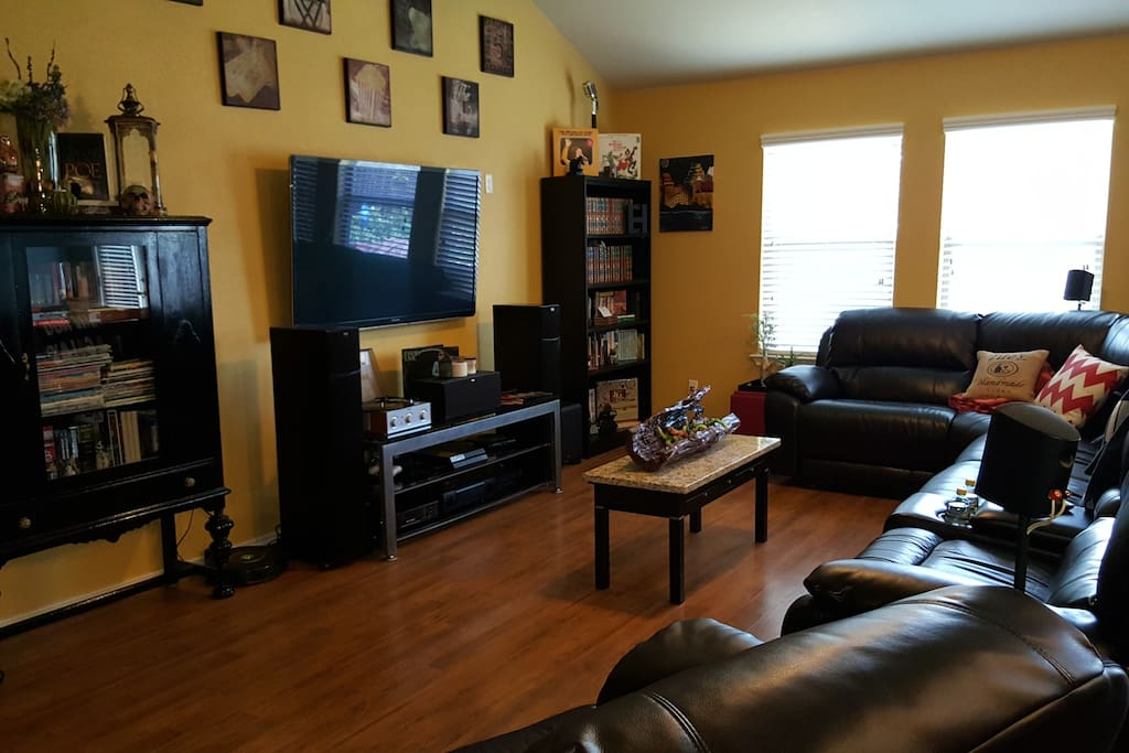 A cozy interactive living room with a 6-seater sectional. 3 chairs are auto-recliners.