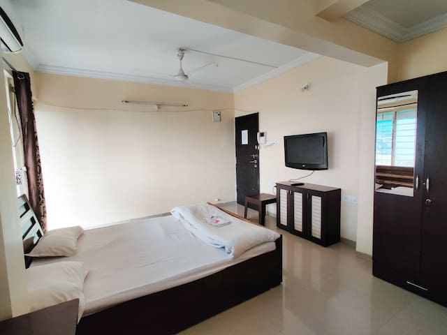 ac bedroom with double bed, tv,  study table, chair, kitchenette, wardrobe and balcony.