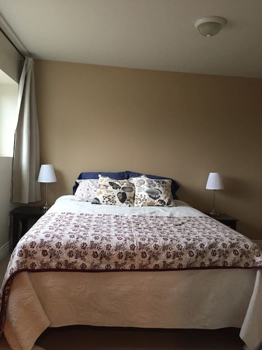 Bedroom with a view.  Queen size bed. two night stands, two lamps and dresser.