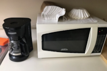 A coffee maker, microwave, paper towels, and coffee filters are available in a kitchenette area.