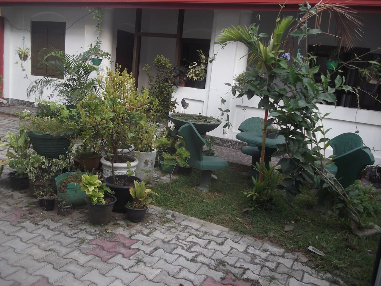 Front view of the property with a part of the well spacious garden with garden chairs and flowering plants which is ideal for relaxation,out door fun and reading books and leissurely thinking